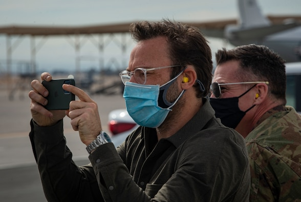 man in mask takes photo with cell phone on flight line