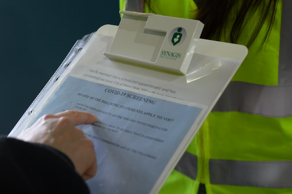 A photo of a clipboard detailing COVID-19 screening questions.