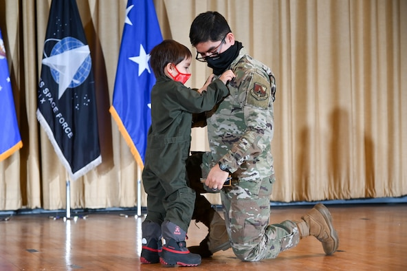 Captain Sergio Martinez, Air Force Life Cycle Management Center, gets his patches replaced by his son at the U.S. Air Force Space Induction Ceremony Feb. 5, 2020