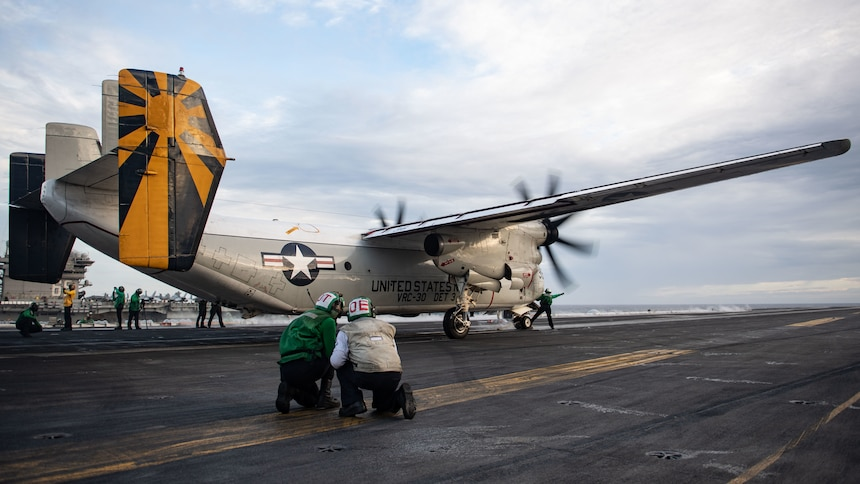 "SOUTH CHINA SEA (Feb. 9, 2021) U.S. Sailors ready a C-2A Greyhound, assigned to the ""Providers"" of Fleet Logistics Support Squadron (VRC) 30, for launch from the flight deck of the aircraft carrier USS Theodore Roosevelt (CVN 71) while conducting dual-carrier operations with the Nimitz Carrier Strike Group in the South China Sea Feb. 9, 2021. The Theodore Roosevelt and Nimitz Carrier Strike Groups are conducting dual-carrier operations during their deployments to the 7th Fleet area of operations. As the U.S. Navy's largest forward-deployed fleet, 7th Fleet routinely operates and interacts with 35 maritime nations while conducting missions to preserve and protect a free and open Indo-Pacific region. (U.S. Navy photo by Mass Communication Specialist 2nd Class Zachary Wheeler)"
