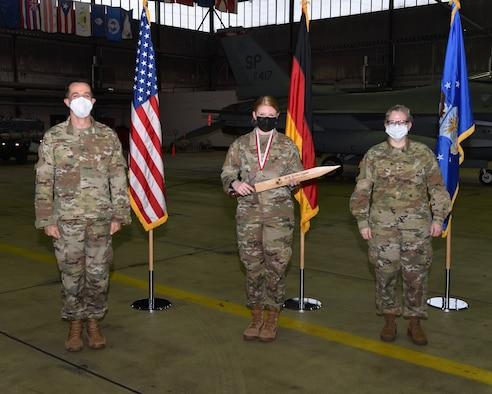 U.S. Air Force Col. Jason Hokaj, 52nd Fighter Wing vice commander (left), and Chief Master Sgt. Stephanie A. Cates, 52nd Fighter Wing command chief (right), give the Airman of the Year award to Senior Airman Kristen Gipson, 52nd Medical Group, Feb. 5, 2021, at Spangdahlem Air Base, Germany.