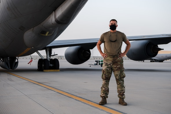 U.S. Air Force Tech. Sgt. stands on flightline posing in COVID mask.
