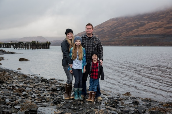 Coast Guard Petty Officer 1st Class Casey Lawrence and her spouse, Justin, also a Coast Guard member, stand with their children on Base Kodiak, Alaska, Nov. 3, 2018. Casey and her family enjoy all that Kodiak has to offer and they recently purchased their retirement home in Kodiak. U.S. Coast Guard photo by Petty Officer 1st Class Charly Hengen.