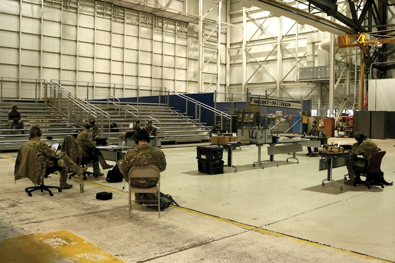 Members of the 445th Aeromedical Evacuation Squadron hold a mission brief in a maintenance bay at Wright-Patterson Air Force Base, Ohio, before heading out on a training flight Jan. 9, 2021. The members socially distanced, wore masks and used their internal radio systems to communicate with each other.