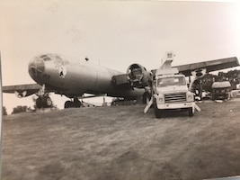 A truck sits in front of a partially deconstructed B-29 Superfortress on a hill.