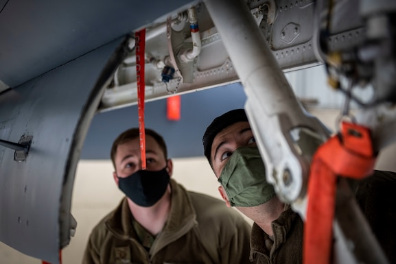 Staff Sgt. William Price (left) and Tech. Sgt. Jorge Gonzalez (right), 4th Fighter Readiness Squadron quality assurance inspectors, perform a safety inspection on an F-15E Strike Eagle at Seymour Johnson Air Force Base, North Carolina, Feb. 4, 2021.