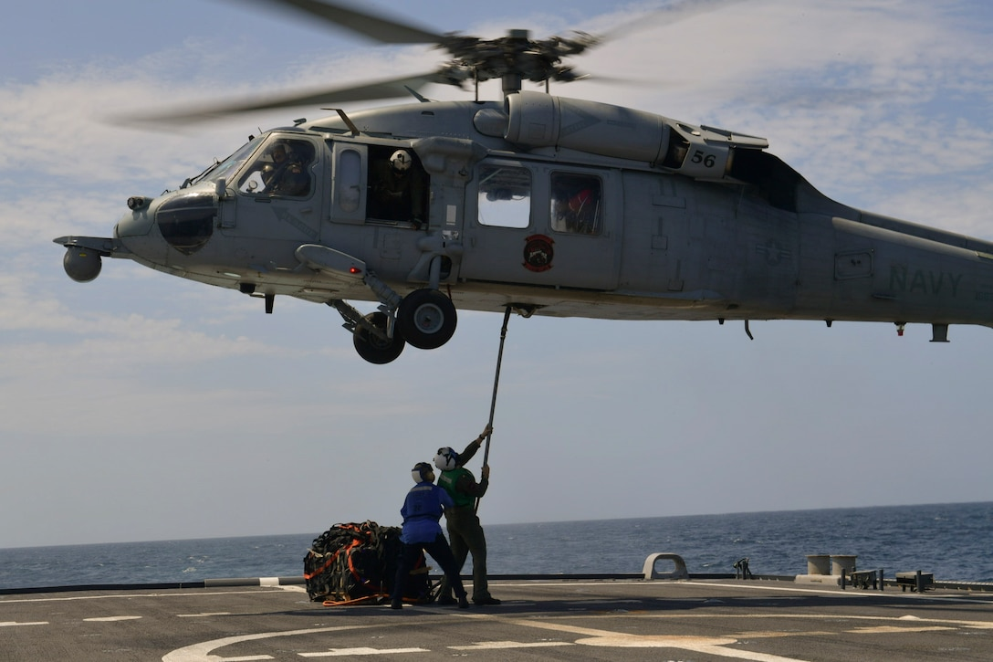 Sailors secure a pallet to a helicopter on the flight deck of a ship.
