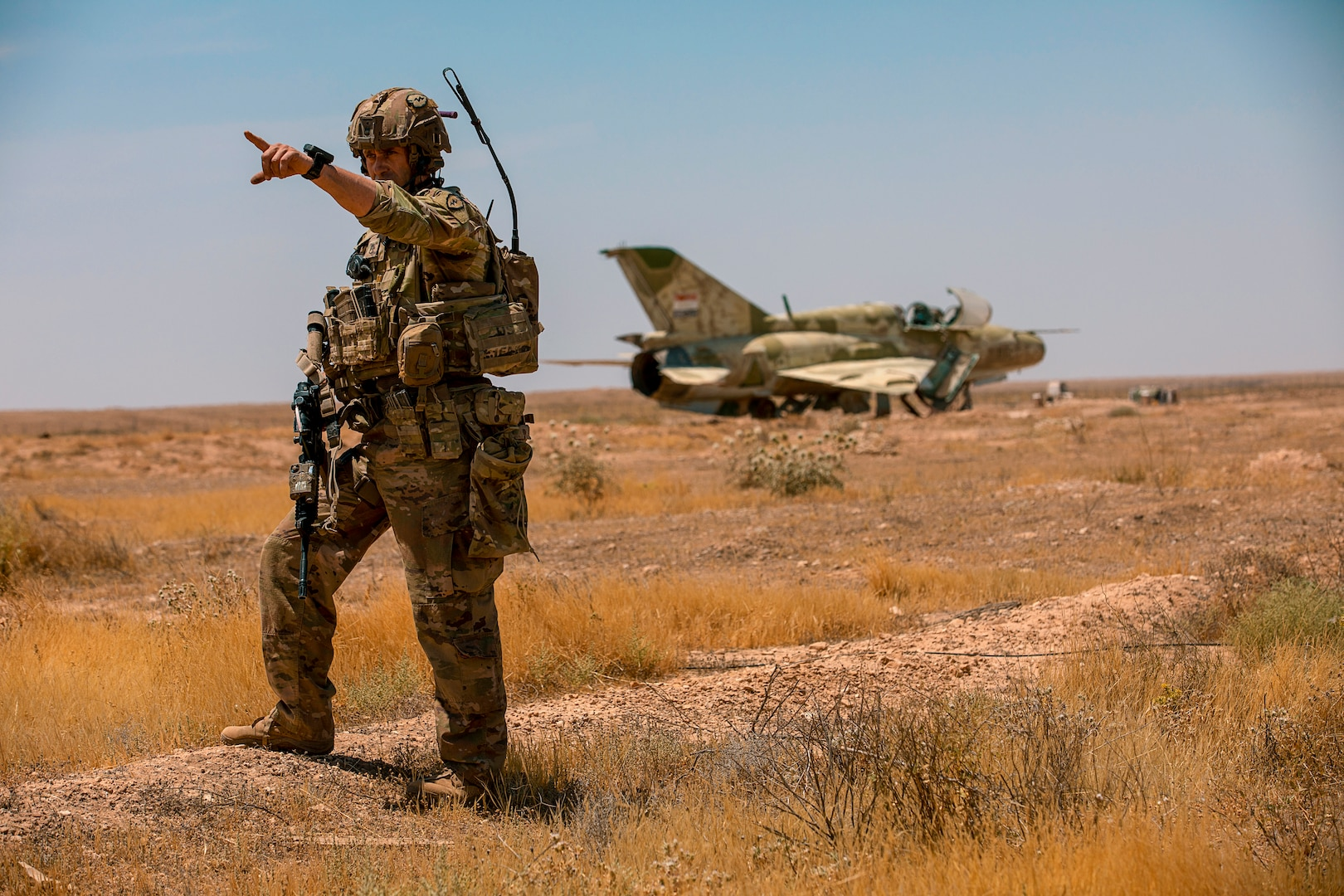 A soldier stands in a dry field and points at something in the distance; behind him, an old aircraft sits rusting in the desert.
