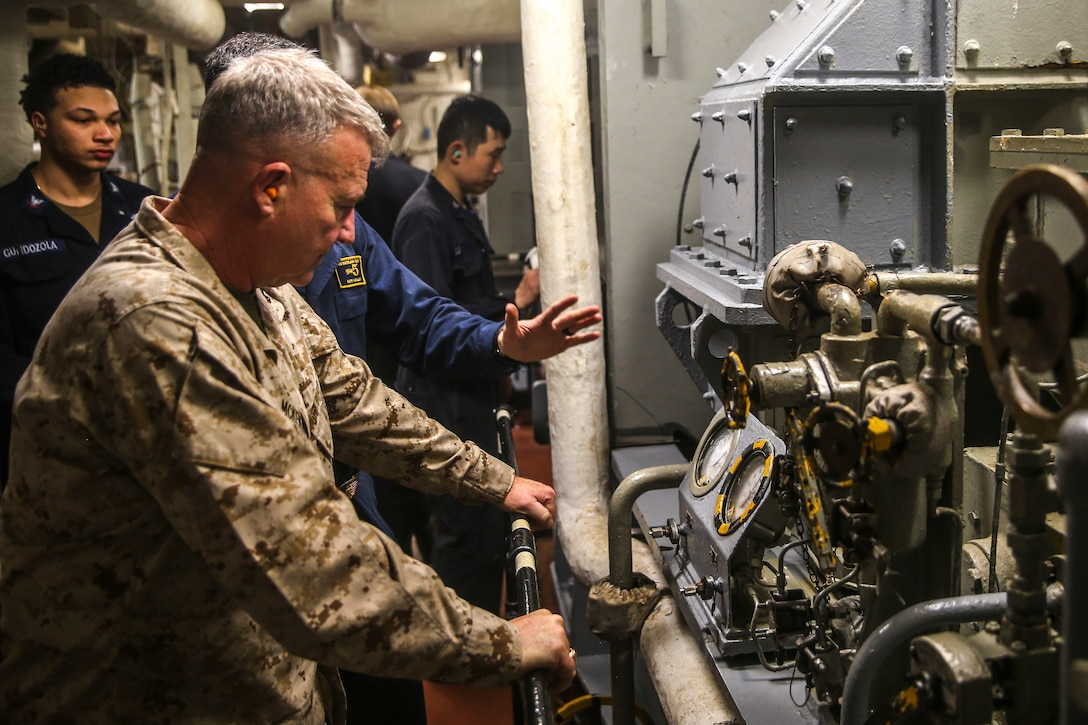A man in a military uniform looks at equipment in a small, enclosed space; four men in uniforms are in the background.