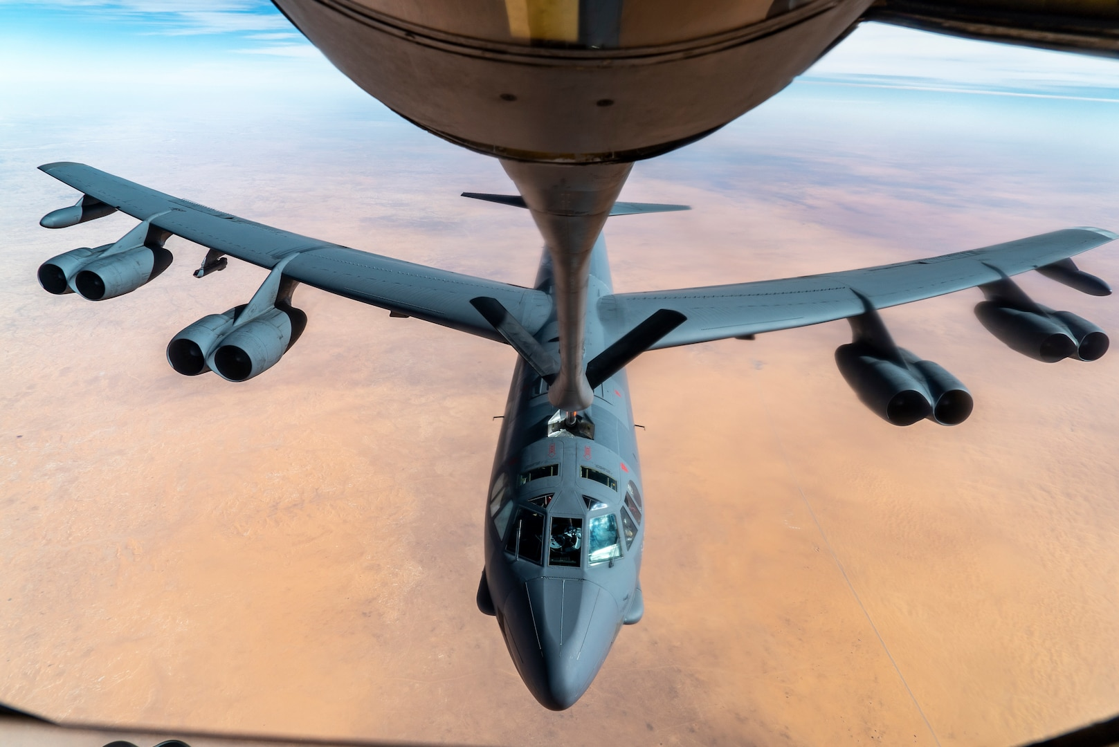 A refueling line extends to a bomber for mid-air refueling.