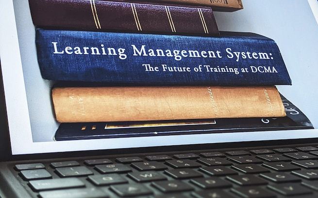 A computer screen shows books, one labeled Learning Management System