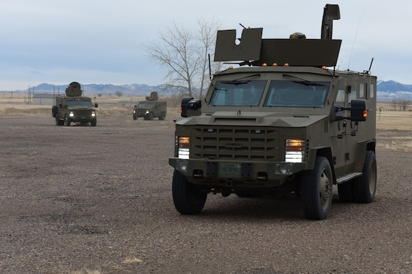 Defends with rifles look into the back of a payload transporter van with the intent of moving into the van and neutralizing the threat.