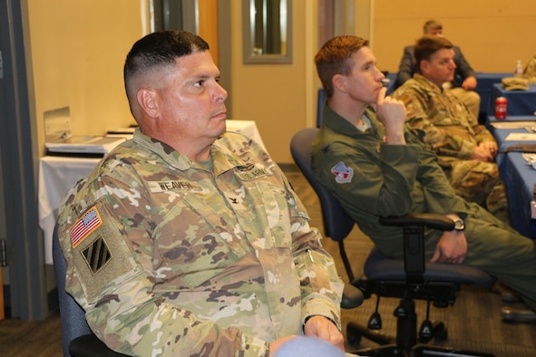 U.S. Army Col. Rick Weaver, Camp Shelby Joint Forces Training Center commander, listens to a speaker during a meeting of the Installation Commanders Counsel at the Combat Readiness Training Center in Gulfport, Miss., Nov. 17, 2020. Seated to Weaver's left are Col. Britt Watson, 186th Refueling Air Wing vice commander, and Col. Tommy Tillman, 172d Airlift Wing Commander.