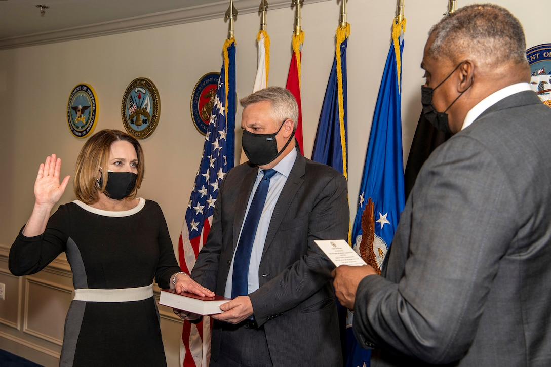 Secretary of Defense Lloyd J. Austin III faces Dr. Kathleen H. Hicks, who raises her right hand and puts her left hand on a book.