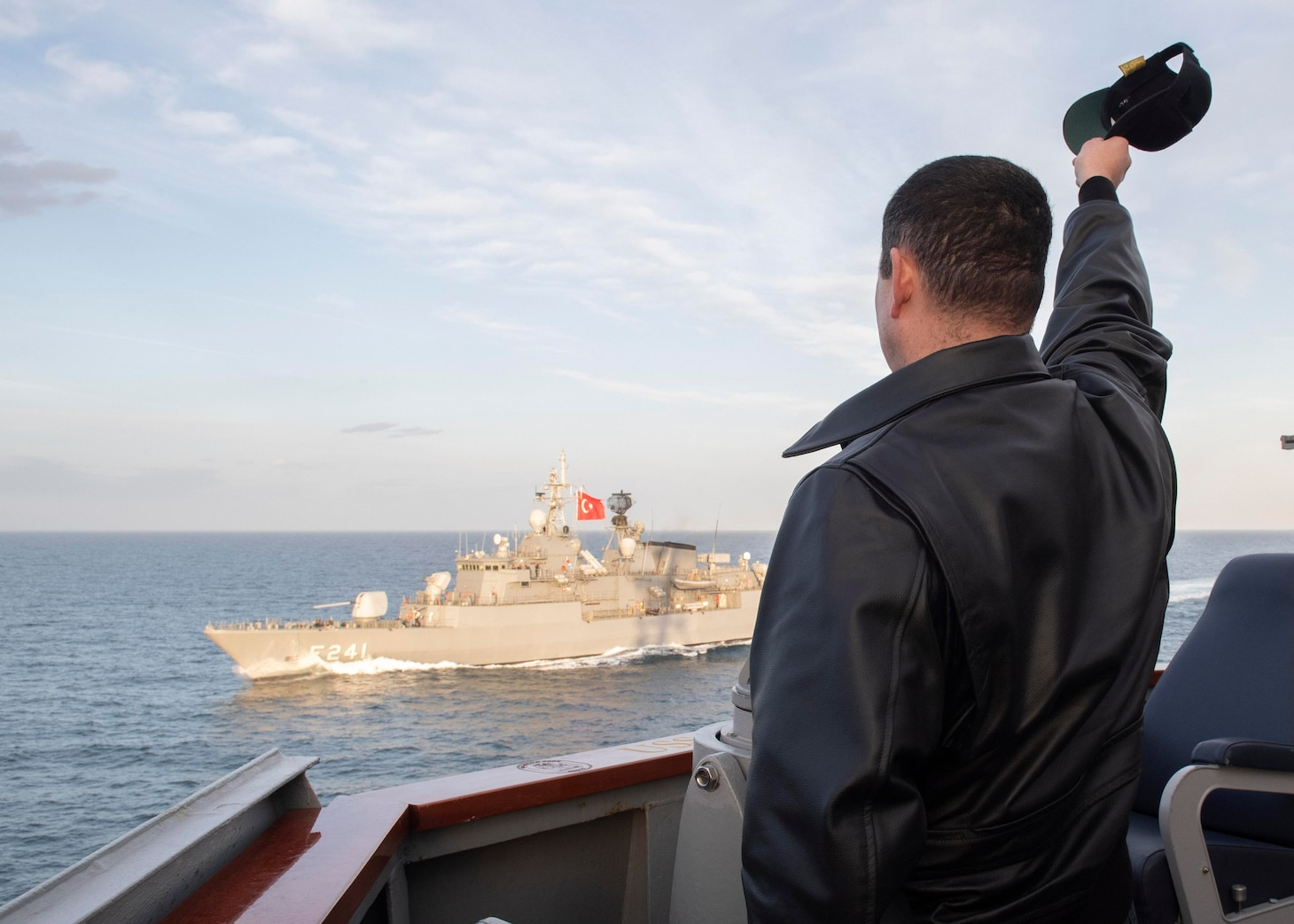 210209-N-RG171-0319 BLACK SEA (Feb. 9, 2021) Cmdr. Matthew Curnen, commanding officer of the Arleigh Burke-class guided-missile destroyer USS Donald Cook (DDG 75), waves to the Turkish navy Yavuz-class TCG Turgutreis (F-241) during a passing exercise in the Black Sea, Feb. 9, 2021. Donald Cook, forward-deployed to Rota, Spain, is on patrol in U.S. Sixth Fleet in support of regional allies and partners and U.S. national security in Europe and Africa. (U.S. Navy photo by Mass Communication Specialist 3rd Class Will Hardy/Released)