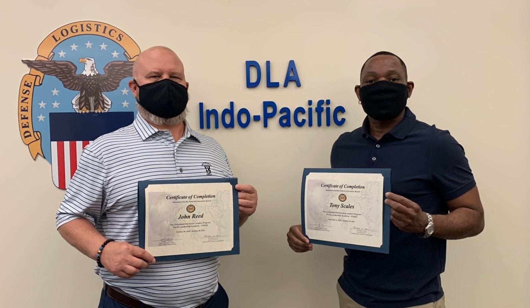 two men hold graduation certificates