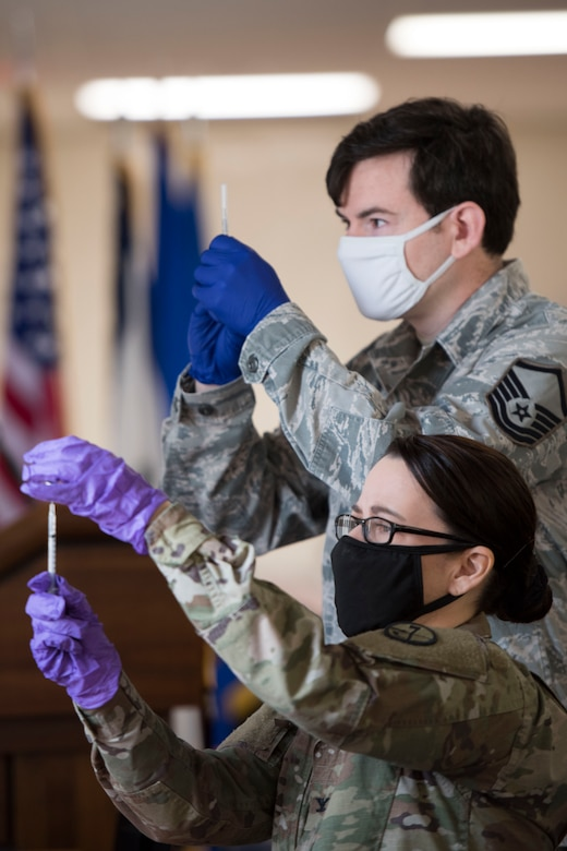U.S. Army Col. Monica Law, a nurse practitioner for the West Virginia National Guard and the officer in charge of the WVNG's Task Force Medical – East, and Master Sgt. Matthew Stickley, a member of the 167th Medical Group and currently assigned to the WVNG's Task Force Medical – East, reconstitute Pfizer mRNA COVID-19 vaccines preparing them to be administered during a vaccination clinic at the 167th Airlift Wing, Feb.6, 2021. (U.S. Air National Guard photo by Senior Master Sgt. Emily Beightol-Deyerle)