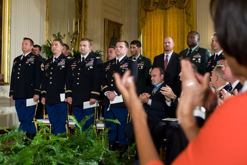 A woman in the foreground applauds as soldiers stand at attention in the background. Others in the audience also applaud.