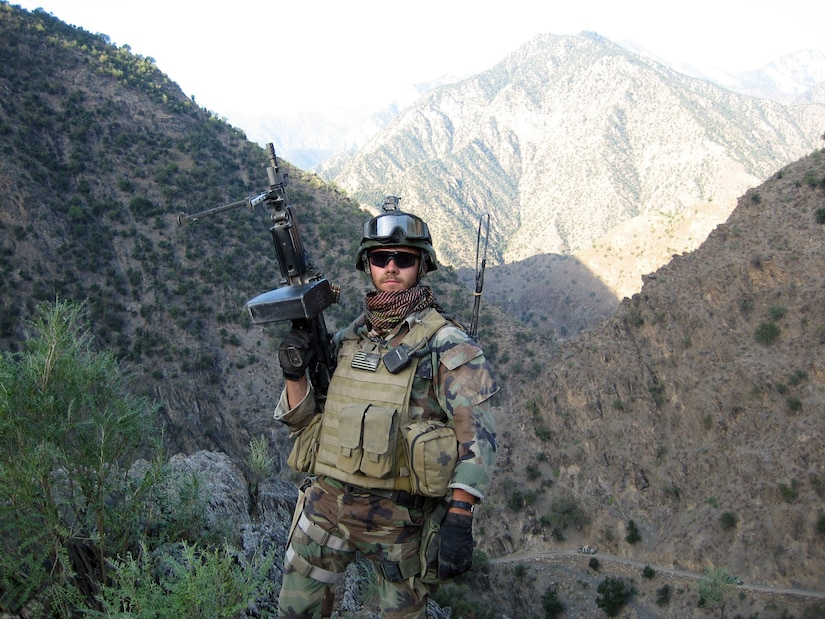 A man in combat gear points a large weapon into the air. Mountains line the background.