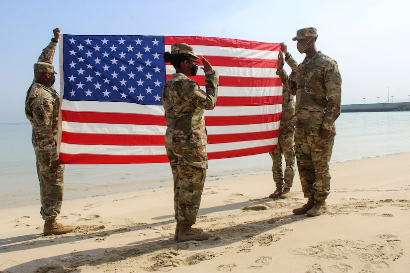 Two soldiers face each other with right hands raised on a beach, as two others hold up an American flag behind them.