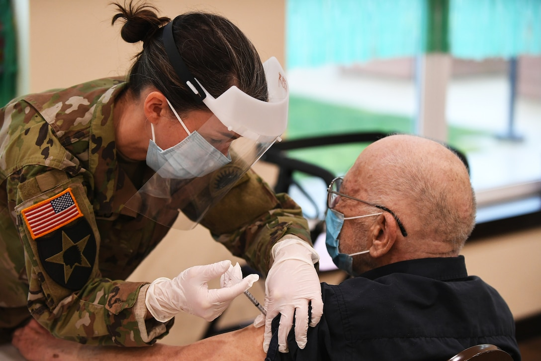 A soldier wearing a face mask and gloves gives a COVID-19 vaccine to an elderly man