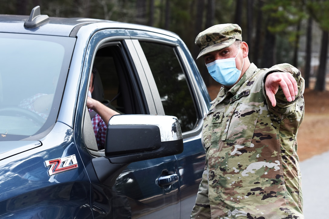 A soldier wearing a face mask directs a vehicle to the COVID-19 mobile testing site