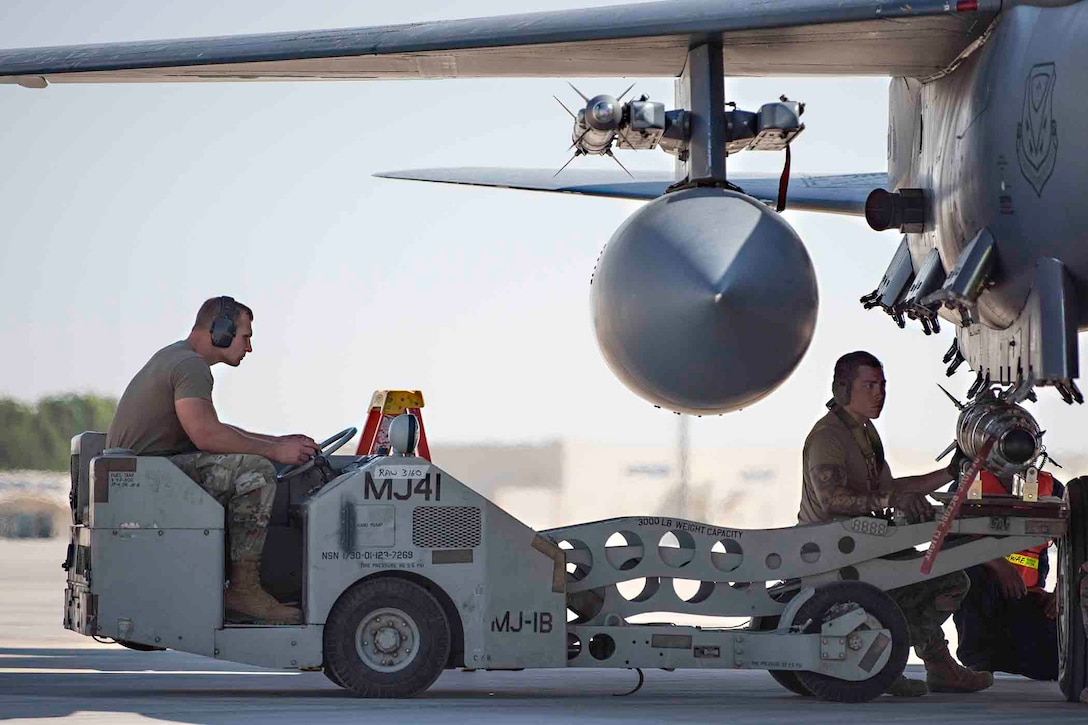 Two airmen load a munition on an Air Force aircraft.
