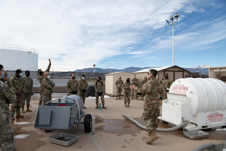 """An Airmen speaks to a small group of soldiers in front of a large white container labeled """"LIQUID OXYGEN"""" and a gray container beside him."""