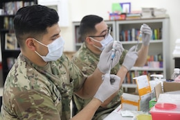 Spc. Michael Meza and Spc. John Cera, healthcare specialists with the 228th Combat Support Hospital, draw doses of the Moderna COVID-19 vaccine from vials at Camp Arifjan, Kuwait, Jan. 18, 2021. Camp Arifjan is utilizing a phased distribution of the vaccine, as specified by the Department of Defense, beginning with medical personnel and first responders.