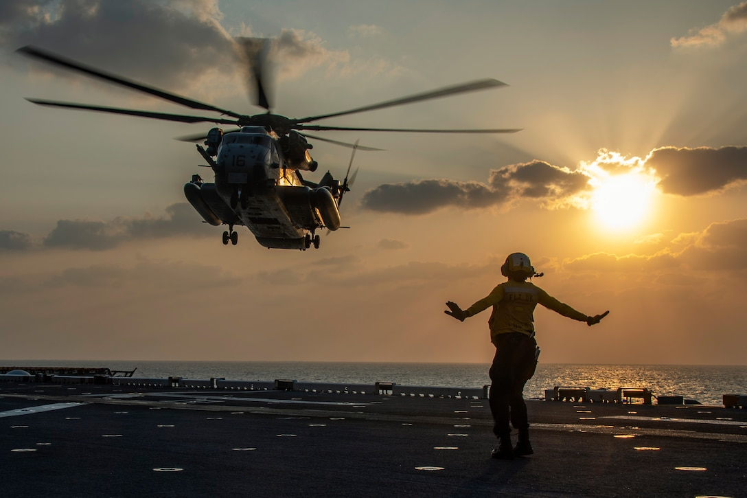 A sailor signals a helicopter to land on a ship.