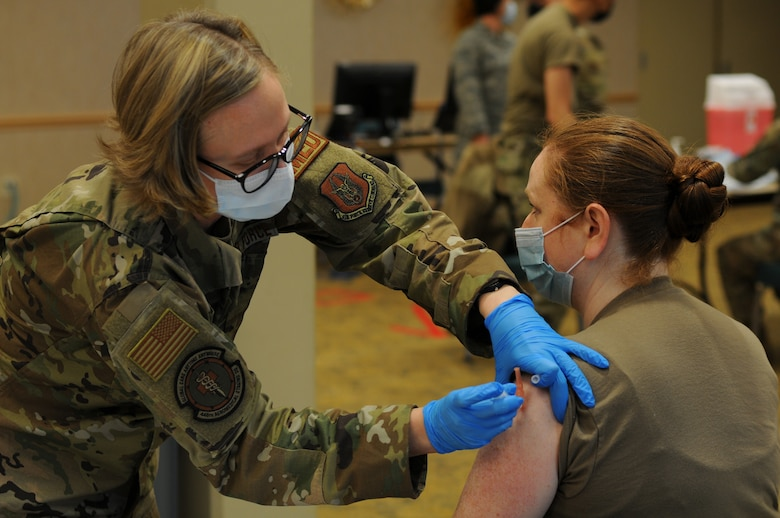 U.S. Air Force Tech. Sgt. Rosemary Nantz, a Reserve Citizen Airman with the 446th Aeromedical Staging Squadron, receives her first dose of the Moderna COVID-19 vaccine from Tech. Sgt. Sarah Hora, an Air Force Reserve medical technician with the 446th Aeromedical Staging Squadron, at Joint Base Lewis-McChord, Washington, Feb. 6, 2021