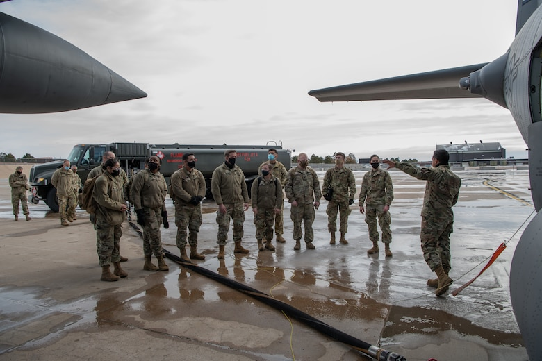 An Airman speaks to a small group of soldiers on the flight line with a fuel truck in the background and a C-130 in the foreground with a large fuel hose leading from the truck to aircraft.