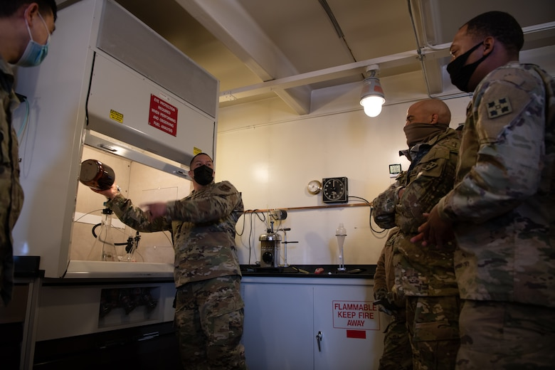 An Airman holds a brown jar inside of a specialized aircraft fuel testing machine, speaking in a small room to two soldiers.