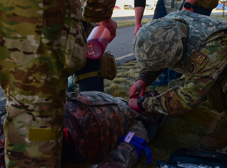 A medic participating in the 2021 Tactical Combat Casualty Care exercise creates an incision in the neck of a medical manikin to open its airway on Buckley Air Force Base, Colo., Feb. 4, 2021.