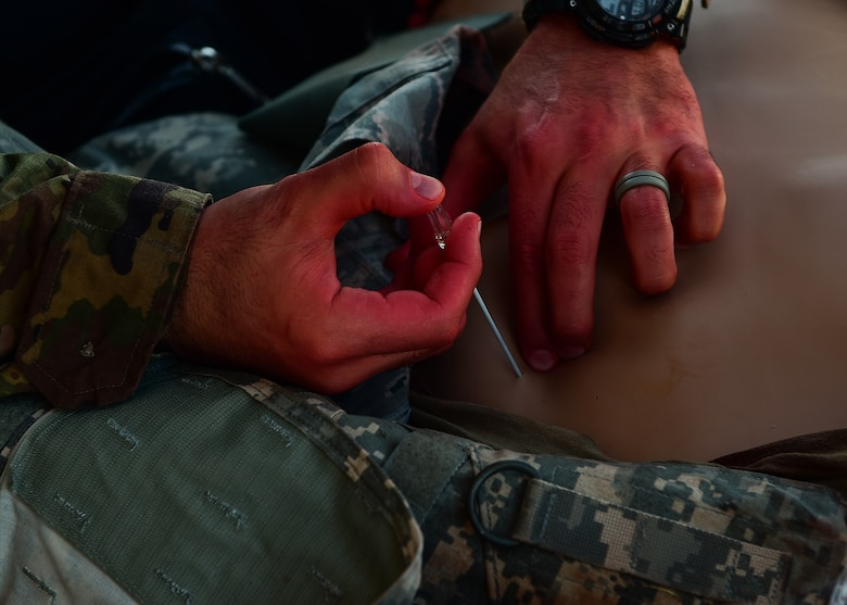 A medic participating in the 2021 Tactical Combat Casualty Care exercise treats a medical manikin with air in the chest cavity using needle decompression on Buckley Air Force Base, Colo., Feb. 4, 2021.