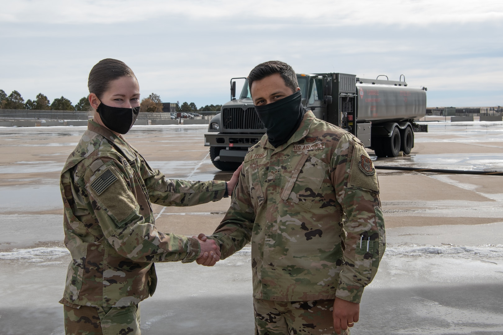 A soldiers shakes the hand of an Airman with a fuel truck in the background on the flight line.