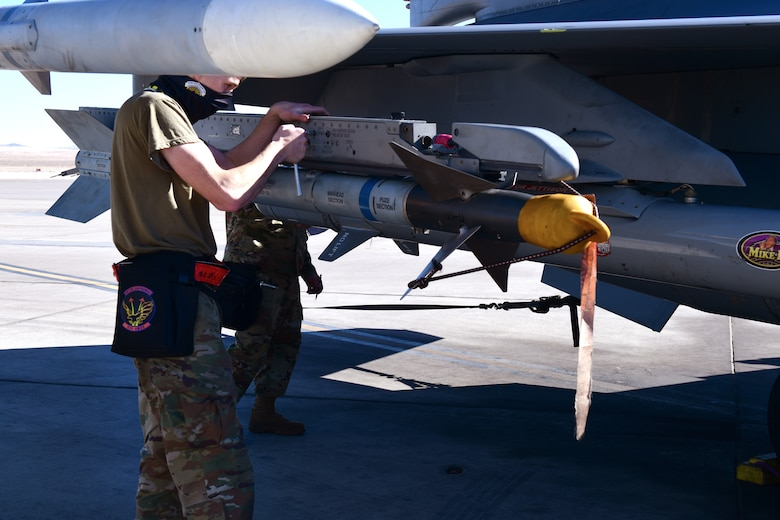 Senior Airman Kaleb Moyer, 926th Aircraft Maintenance Squadron, removes a weapon from an F-16, Feb. 6, at Nellis Air Force Base, Nevada.