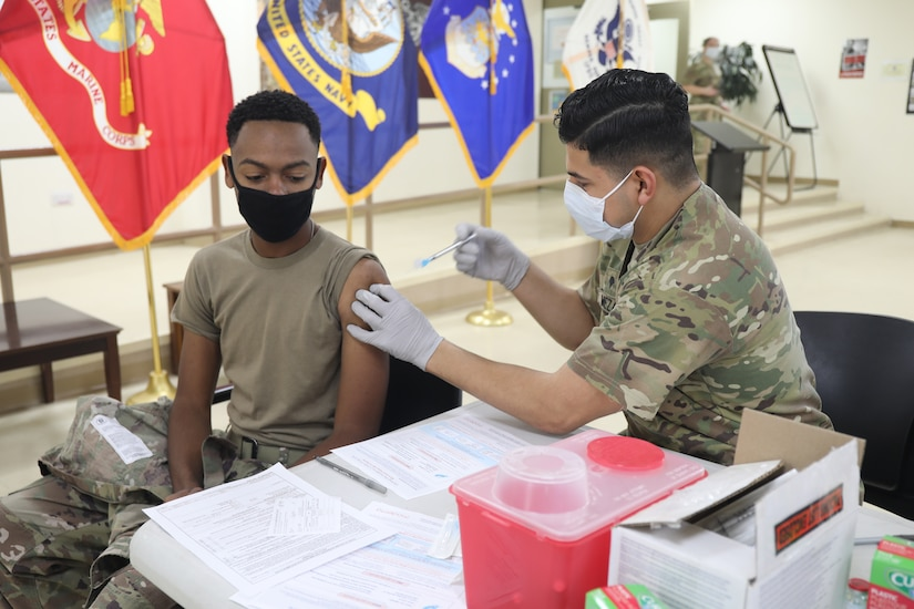 Spc. Michael Meza, healthcare specialist, 228th Combat Support Hospital, administers the Moderna COVID-19 vaccine to Spc. Sarrod Hearn, radiology specialist, 228th Combat Support Hospital, at Camp Arifjan, Kuwait, Jan. 18, 2021. Camp Arifjan is utilizing a phased distribution of the vaccine, as specified by the Department of Defense, beginning with medical personnel and first responders.