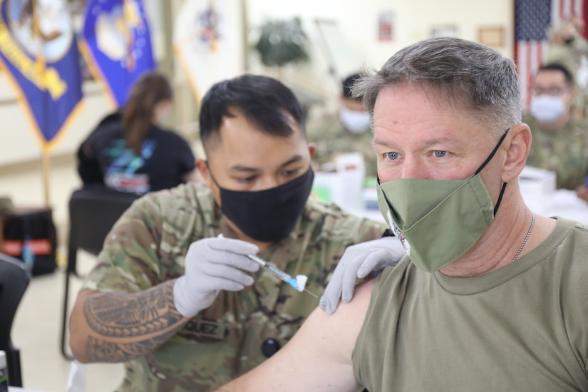 Spc. Vincebryan Marquez, healthcare specialist, 228th Combat Support Hospital, administers the Moderna COVID-19 vaccine to Lt. Col. Scott Gadberry, anesthesiologist, 228th Combat Support Hospital, at Camp Arifjan, Kuwait, Jan. 18, 2021. Camp Arifjan is utilizing a phased distribution of the vaccine, as specified by the Department of Defense, beginning with medical personnel and first responders.