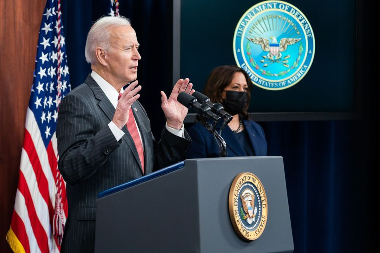 President Joe Biden speaks while Vice President Kamala Harris stands to his right.