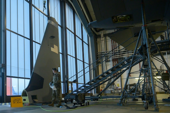 An Airman examines a C-130 tail.