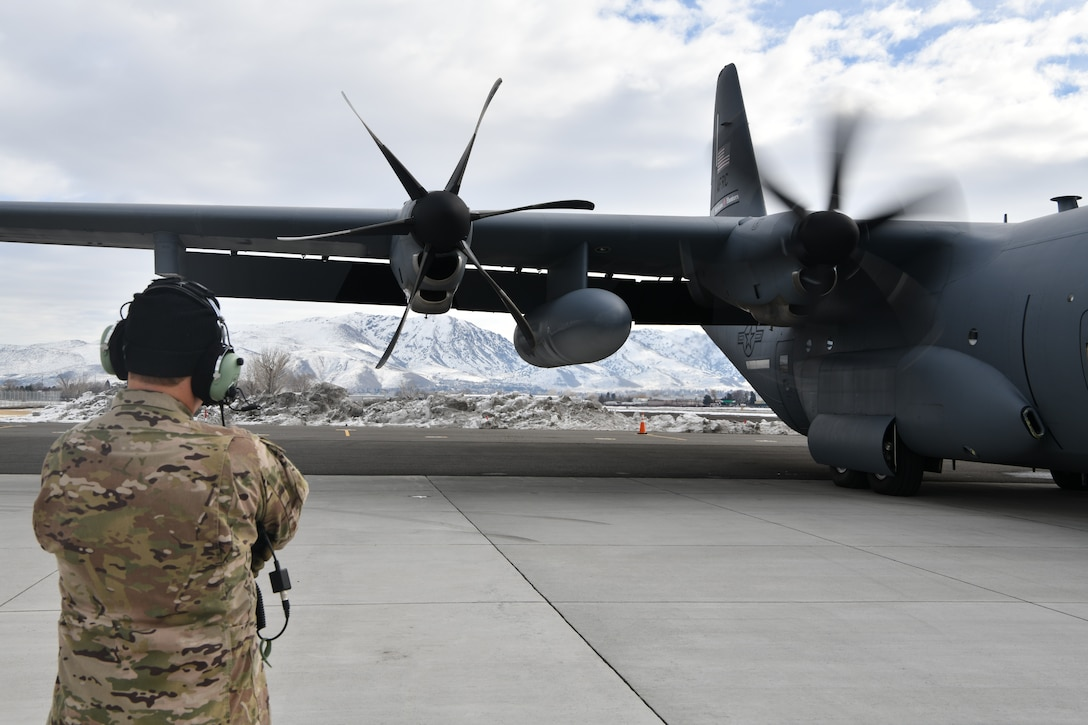 """Master Sgt. Chris Becvar, loadmaster for the 53rd Weather Reconnaissance Squadron at Keesler Air Force Base, Miss., looks on as the propellers begin to turn on a WC-130J """"Hurricane Hunter"""" at Reno-Tahoe International Airport, Nev., Jan. 31, 2021. As a loadmaster Becvar is responsible for a multitude of tasks including monitoring the aircraft's operability in flight as well as dropping dropsondes from a specialized pallet to collect weather data. (U.S. Air Force photo by Staff Sgt. Kristen Pittman)"""