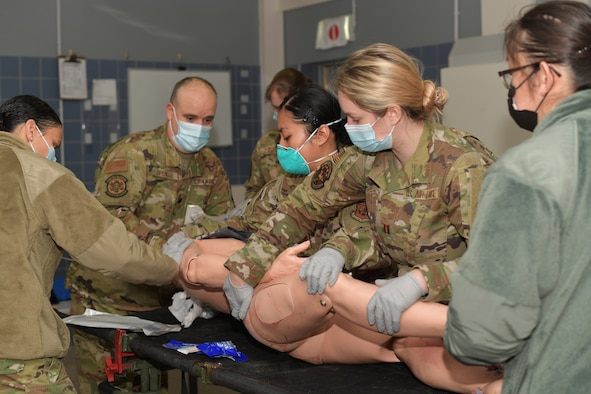 Airmen standing around a simulated medical patient mannequin.