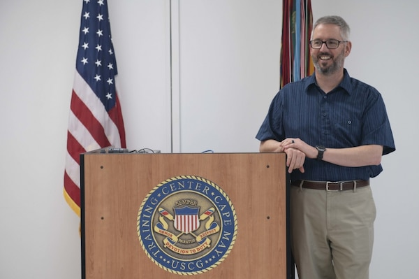 Matt Smith, the Civilian of the Quarter for April - June 2020, poses behind his teaching podium Aug. 11, 2020, aboard Training Center Cape May, New Jersey. Our Training Center staff serve the American public by leveraging their talent and passion to produce mission-ready recruits, and delivering professional, high-quality services to enable future missions for our units, tenants, and regions. (U.S. Coast Guard photo by Petty Officer 2nd Class Shannon Kearney)