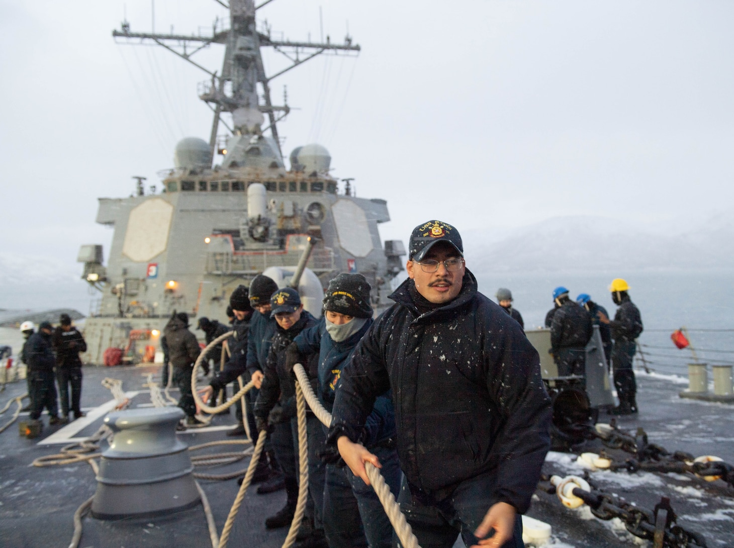 Sailors assigned to the Arleigh Burke-class guided-missile destroyer USS Ross (DDG 71) heave in storm lines in preparation to get underway