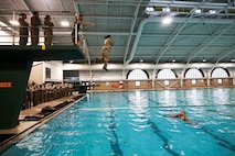A recruit with November Company, 4th Recruit Training Battalion, jumps off the tower during basic swim qualification aboard Marine Corps Recruit Depot Parris Island, S.C. Jan. 13, 2021. The tower is used to simulate aborting a ship at sea and is followed by a 25 meter swim. (U.S. Marine Corps photo by Lance Cpl. Samuel C. Fletcher)