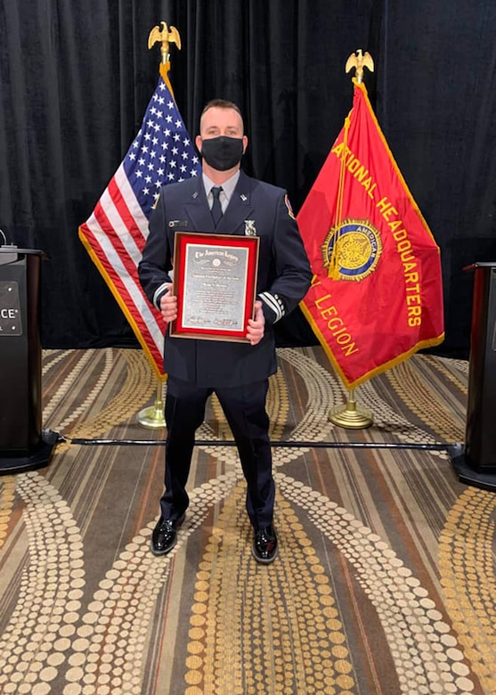 Firefighter poses with an award