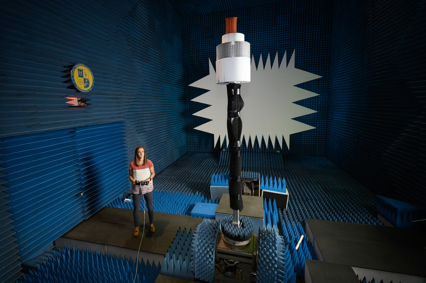 U.S. Naval Research Laboratory electrical engineer makes adjustments to an array inside the anechoic chamber.