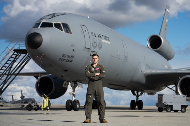 Airman posing for photo in front of an aircraft