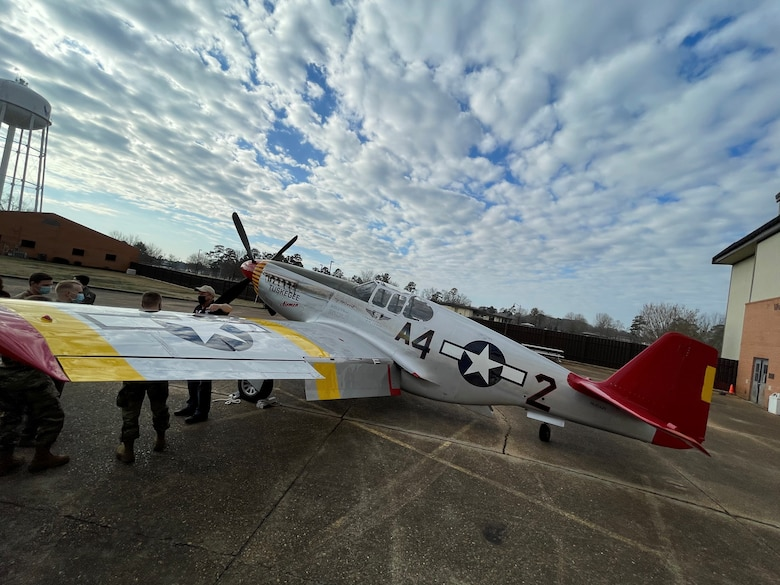 """Air Force members talk amongst one another while a P-51C Mustang sits on the Columbus Air Force Base, Miss. flightline, during a static display on Feb. 10, 2020. The Commemorative Air Force Red Tail Squadron's P-51C, named """"Tuskegee Airmen"""", is an authentic and fully restored operational fighter from the World War II era. (U.S Air Force photo by Tech Sgt. Javier Cruz)"""